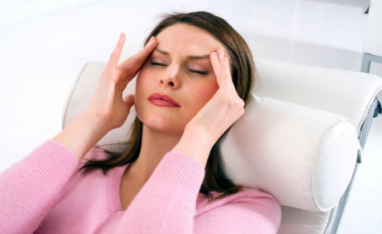 mulher deitada massageando suas têmporas aparentando dor ou desconforto